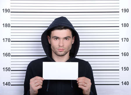 Busted burglar. Angry burglar holding a white poster while standing against police line-up photo