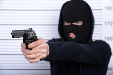 Busted burglar. Angry burglar threatens arms standing against police line-up photo