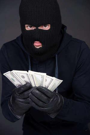 dinero falso: Criminal con un pasamonta�as con un pu�ado de dinero conceptual del bot�n de un robo corrupci�n soborno rescate recompensa coacci�n o la mafia dinero de protecci�n