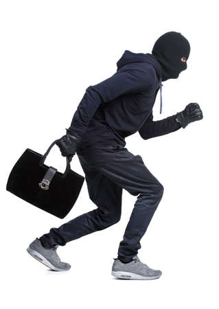 Portrait of running male burglar with a handbag. Isolated on white background Stock Photo - 28277603