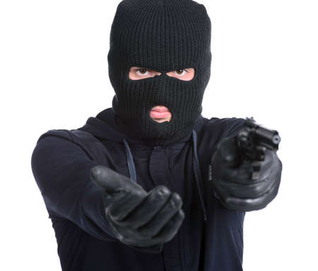 hijacker: Masked robber with gun aiming into the camera against a white background