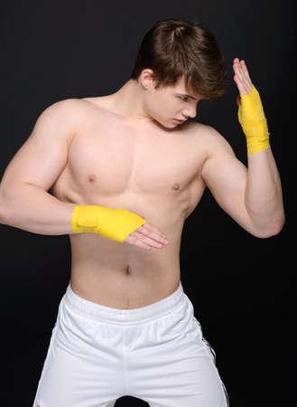 Sportsman kick boxer intense portrait against black background. photo