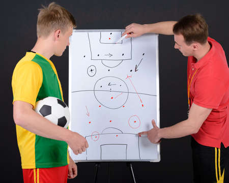 soccer coach: Soccer coach training with soccer men. Isolated on black background Stock Photo