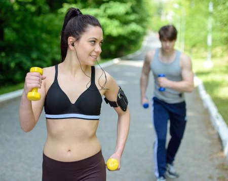 hombre flaco: Mujer joven y hombre corriendo en el parque Foto de archivo