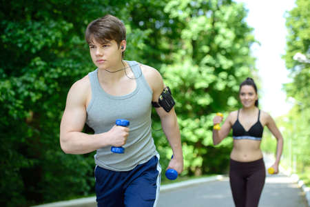 Young woman and man running in park photo