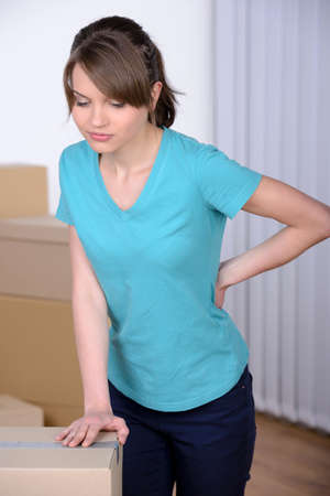expressing negativity: Pain in back. Young woman holding hand on his back and expressing negativity while leaning at the cardboard box