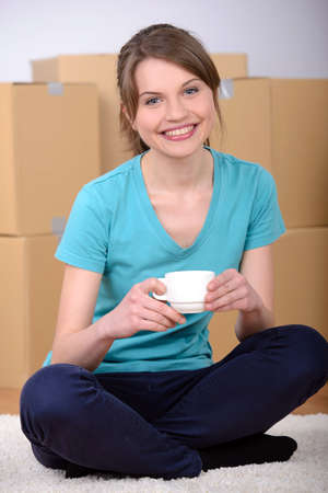 Beautiful single young woman drinking tea or coffee unpacking boxes and moving into a new home. photo