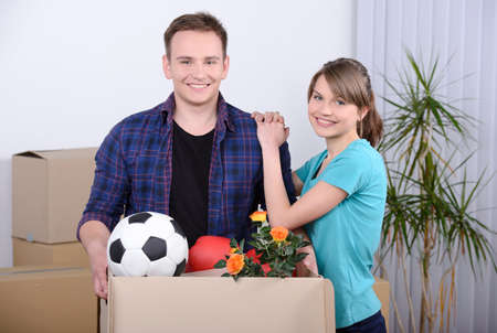 Moving to a new apartment. Beautiful young couple standing close to each other and smiling at camera while holding cardboard boxes photo