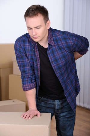 expressing negativity: Pain in back. Young man holding hand on his back and expressing negativity while leaning at the cardboard box Stock Photo