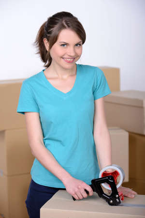 sealing tape: Woman sealing boxes ready for house move Stock Photo