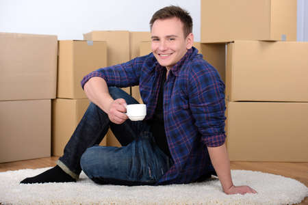 Young man, drinking tea, unpacking boxes moving to a new home photo