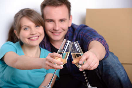 Celebrating their moving. Beautiful young couple sitting on the floor and drinking wine while cardboard boxes laying around them photo
