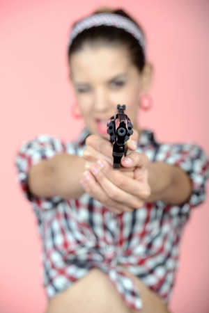 Gangster woman with pistol isolated on pink background photo