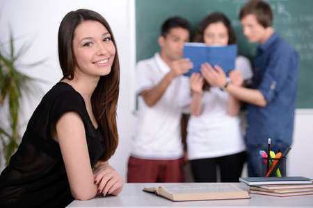 Group young students while studying in classroom photo