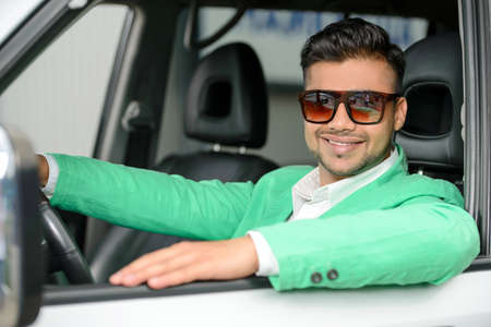 Portrait of young Indian business man, driving a car photo