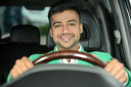 Portrait of young Indian business man, driving a car Stock Photo