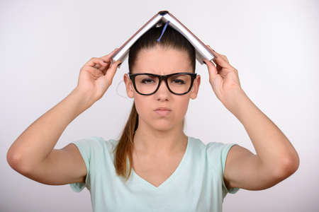 Beautiful female student in glasses cover her head with book photo
