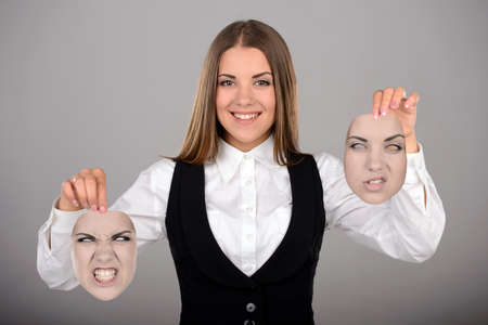 dissimulation: Young businesswoman holding two masks with different emotions to choose from today. Gray background
