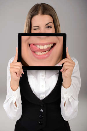 Increase emotions. Business woman holding a tablet with the increase of its emotions. Gray background photo