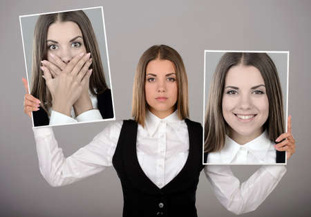 dissimulation: A young business woman holds two portraits of different emotions to choose from today. Gray background
