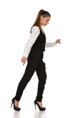 Business woman walking along a tightrope, isolated on a white background. photo