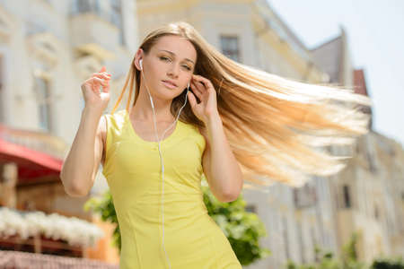 Young beautiful woman listening to music in the city, outdoors photo
