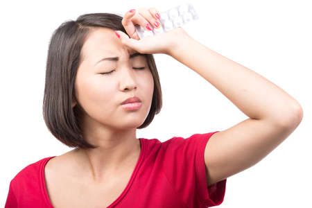 Portrait of young asian woman is suffering from a headache. On the white background. photo