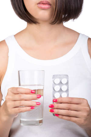 Young girl is holding a glass of water and tablets in hands. On the white background. photo