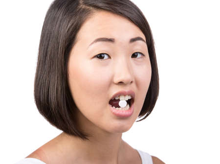 Asian young woman is taking pills, isolated on white.  Close-up. photo