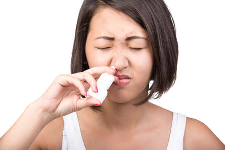 Asian woman is suffering from colds and runny nose. Portrait on white background. photo