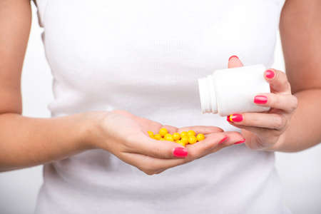 Close-up woman in white is taking the yellow pills, vitamins. photo