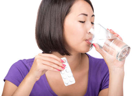 Taking medication. Asian young woman with glass of water takes pills, isolated on white. Stock Photo