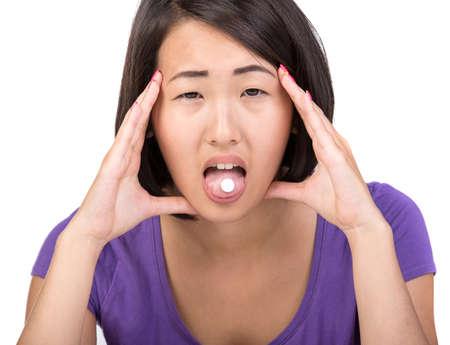 Young asian woman has headache. She ia taking medication. photo