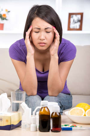 Young asian woman treats colds. She is taking medications. Medicines and lemons on the table. She has headache. photo