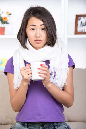 Pretty asian woman is sick. She is drinking hot tea at home. photo