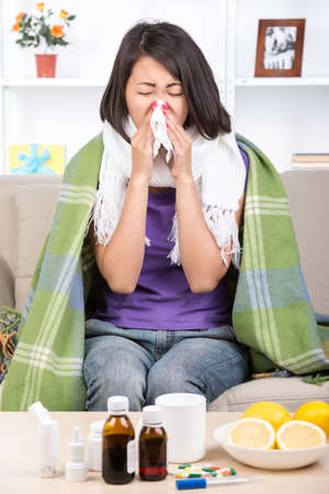 Young asian woman treats colds. Medicines and lemons on the table. photo