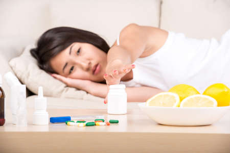 Asian woman is sick. She needs medication. Medicine are on the table. photo