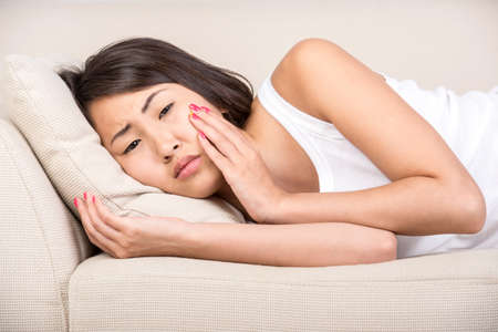 head pain: Young asian woman has toothache. She is lying on the bed.