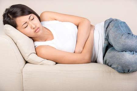 dolor de estomago: Mujer joven asiática está sufriendo de dolor en el estómago, que está tumbado en la cama.