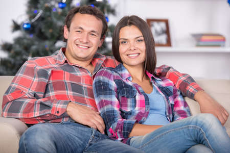 Portrait of lovely couple in christmas time. Christmas tree and gifts in background. photo