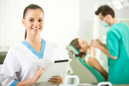 非常に看護師は笑みを浮かべてカメラを見ています。歯科医と患者の背景に。