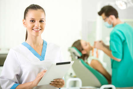 Pretty nurse is looking at camera with smile. Dentist and patient on background.