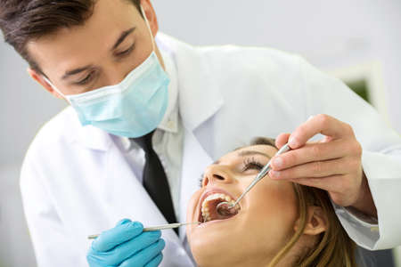 Portrait of a dentist who treats teeth of young woman patient. photo