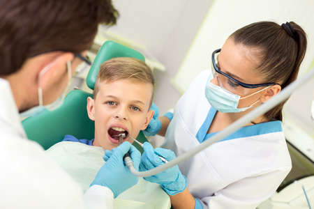 Dentist and nurse are curing a little boy patient. photo