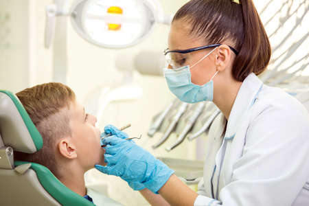 The female doctor treats a tooth of little boy at dentists clinic. photo