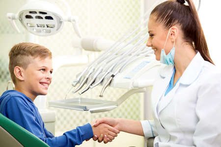 Portrait of friendly doctor and little boy patient at dentists office.