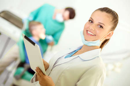 Pretty nurse with tablet, looking at camera with smile. Dentist and patient on background.