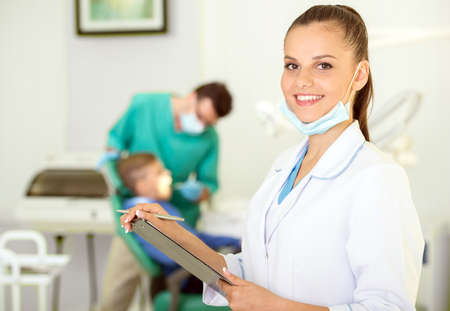 A portrait of a dental assistant is smiling at the camera with the dentist working in the background.