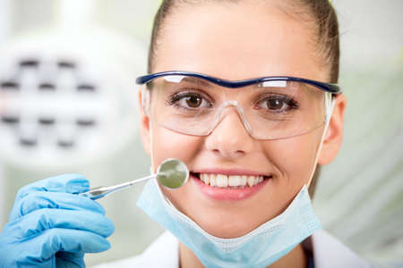 A portrait of the smiling woman dentist at her office. Close-up.