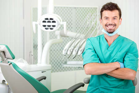 A portrait of the smiling young man, dentist at his office. photo